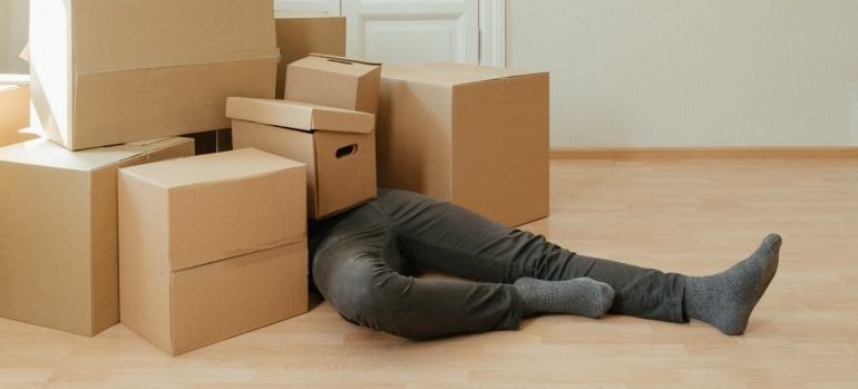 man covered with moving boxes