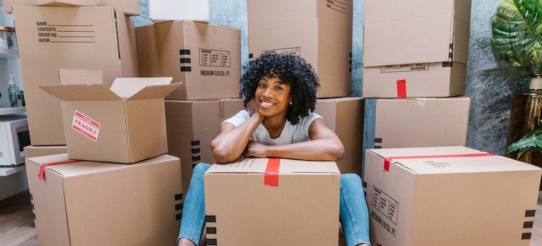 a woman sitting on the floor surrounded by boxes