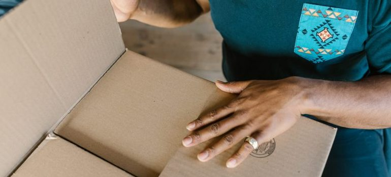mover packing a cardboard box