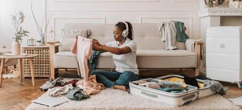 Women is preparing to move long distance and packing while listening to music