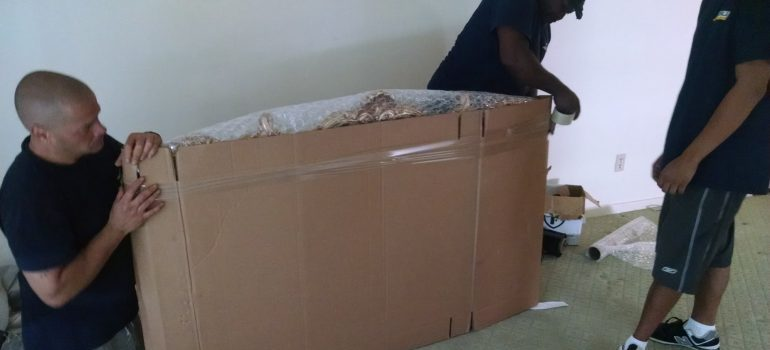 movers packing items in a huge box